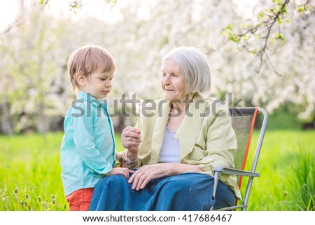 Little boy blowing dandelion seeds while his great grandmother is holding a flower