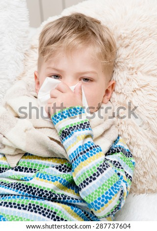 Little boy blowing his nose - stock photo