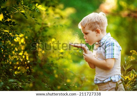 Little boy blows gold glitter from his hands.