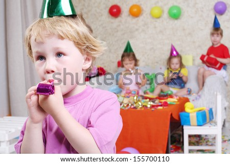 Little boy blows in party blowers at birthday party and three girls sit on couch. Inscription Happy Birthday on wall. Focus on boy. - stock photo