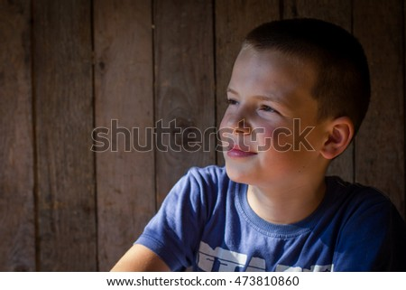 Little boy boy portrait. Old wooden background in behind