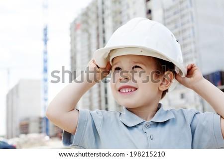Little boy builder in helmet at construction site - stock photo