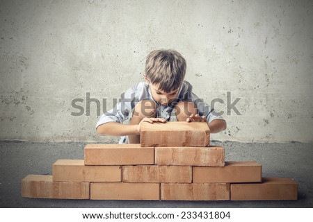Little boy building a house  - stock photo