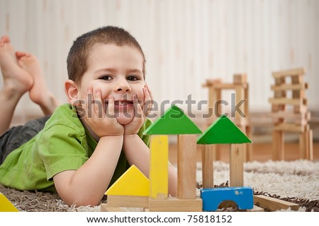 little boy building a house with colorful wooden blocks - stock photo