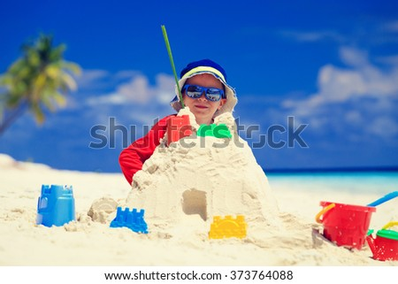 little boy building sandcastle on beach