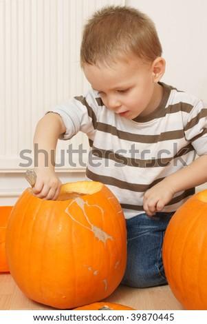 little boy carving pumpkin - stock photo