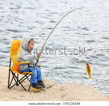 Little boy catching a fish. Happy vacations concept. - stock photo