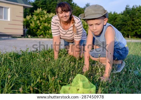 Little boy catching insects in a net with his mother as they both crouch down in the fresh green spring grass as he makes his catch
