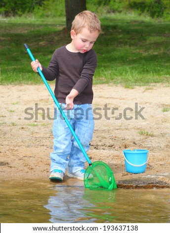 Little boy catching little fish. - stock photo