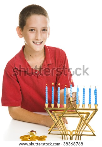 Little boy celebrates Chanukah by lighting the candles on his menorah.  Isolated on white. - stock photo