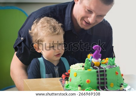 Little boy celebrating his father's second birthday, - stock photo