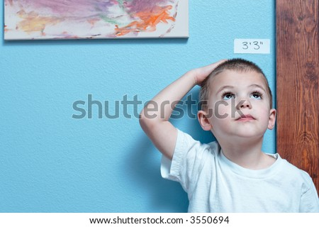 Little boy checking his height against a wall - stock photo
