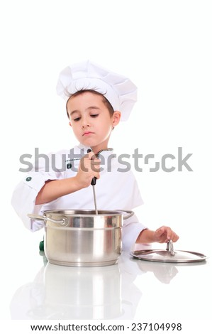 Little boy chef with ladle stirring in the pot isolated on white - stock photo