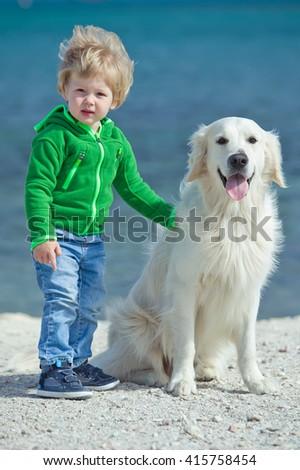 Little boy child and Golden Retriever dog  - stock photo