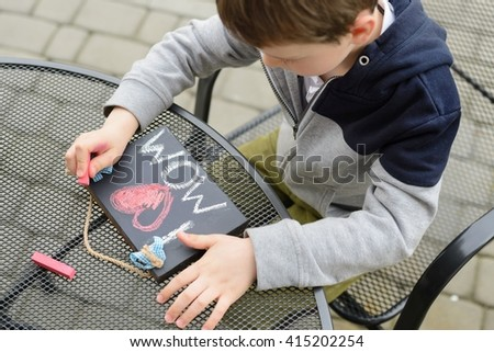 Little boy child drawing a love declaration on small blackboard for his mother on Mother's Day.  - stock photo