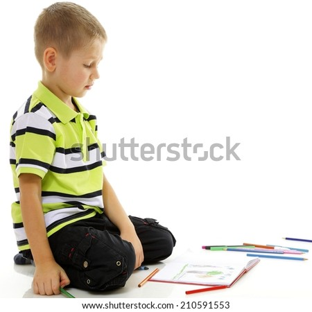 little boy child drawing with color pencils on floor isolated on white background