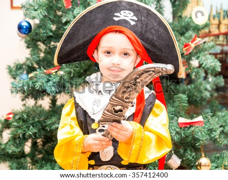 Little boy child dressed as pirate for Halloween  on background of Christmas tree. Kid in carnival costumes for Christmas - stock photo