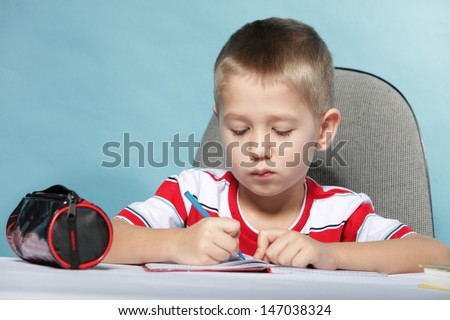 little boy child kid drawing with color pencils on blue background
