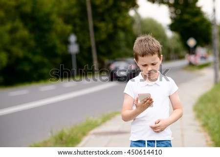 Little boy child playing mobile games on smartphone on the street