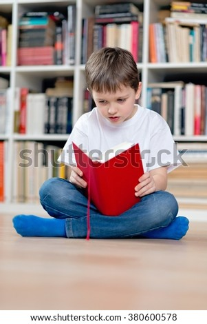 Little boy child reading a red book. He sits cross-legged on the floor. Dressed in a white t shirt and blue jeans - stock photo