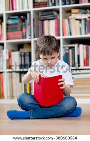 Little boy child reading a red book in the library. He sits cross-legged on the floor. Dressed in a white t shirt and blue jeans - stock photo