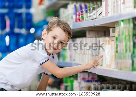 Little boy chooses cosmetics on the shelves of the store
