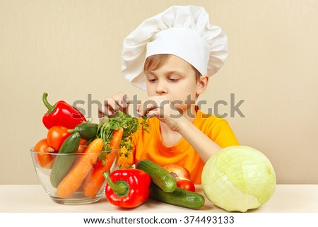 Little boy chooses fresh vegetables for salad at the table