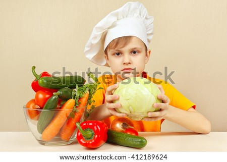 Little boy chooses vegetables for salad at the table - stock photo