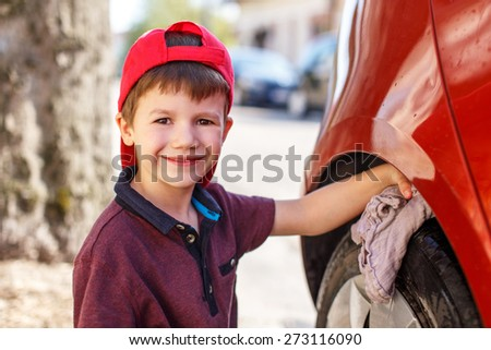 Little boy cleaning red car, summer portrait, car wash - stock photo