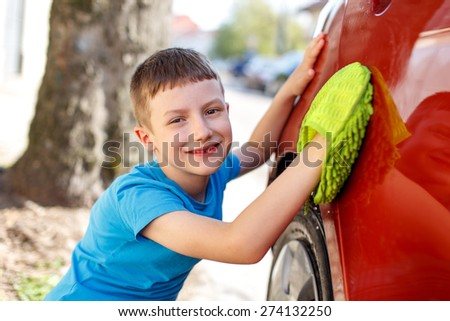 Little boy cleaning red car, summer portrait, polishing car - stock photo