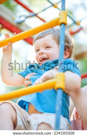 Little boy climbing ladder - stock photo