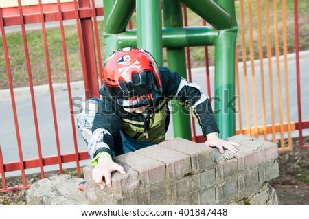 Little boy climbing on a brick wall on outdoors - stock photo