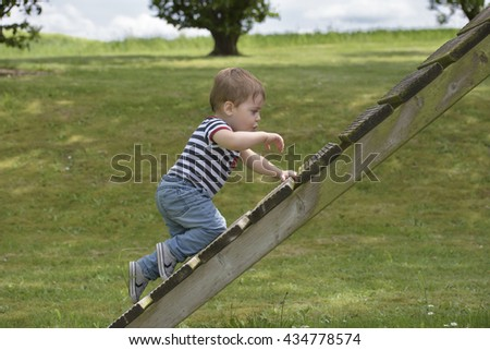 Little boy climbing on garden toys