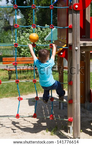 Little boy climbing on rope at playground, dangerous - stock photo