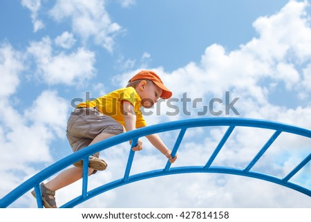 little boy climbs up the ladder on the playground. child climbs confidently up the ladder against the blue sky. copy space for your text - stock photo