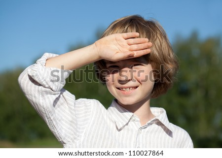 Little boy closes his hand from the bright sun - stock photo