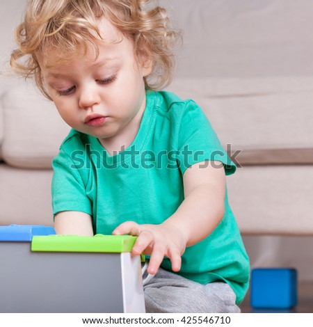 Little boy concentrated on playing with toys - stock photo