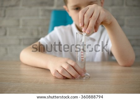 Little boy conducting experiment on water, Checks its acidity and ph - stock photo