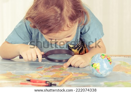 little boy considering a world map with a magnifying glass at home - stock photo