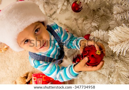 Little boy considers gifts, while celebrating Christmas at home - stock photo