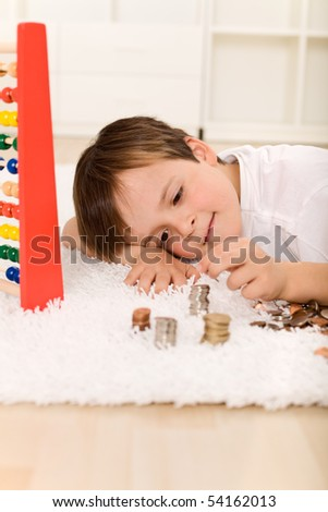 Little boy counting his money laying on the floor building coin columns - stock photo