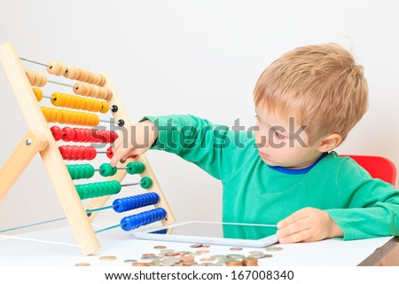 Little boy counting his savings  - stock photo