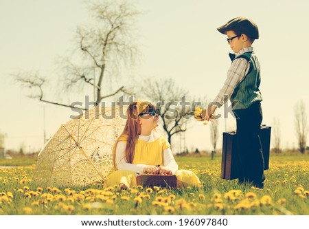 little boy courting a girl of the park in a flower meadow.vintage-look / little romance - stock photo