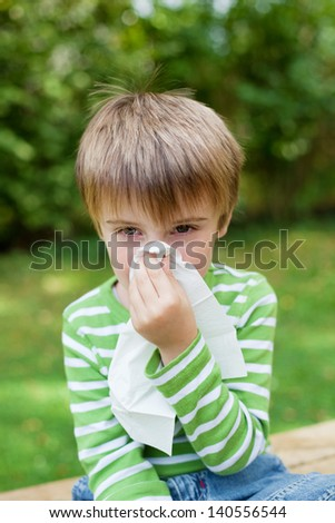 Little boy covering his nose because of allergy - stock photo