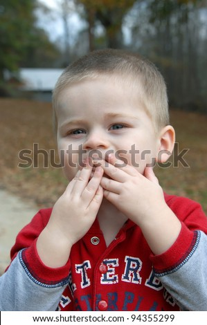 "Little boy covers his mouth with both hands to ""blow a kiss"".  He has close cropped hair and is wearing a red and grey jacket. - stock photo"