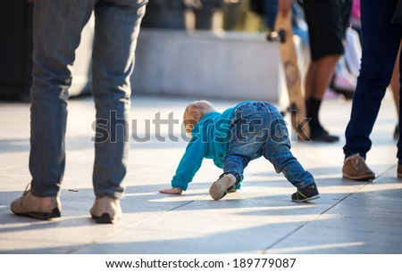 Little boy crawling among people