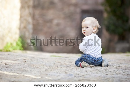 Little boy crawling on stone paved sidewalk - stock photo