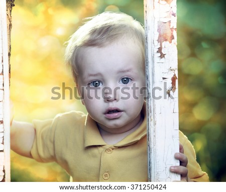 Little boy crying  in garden. - stock photo