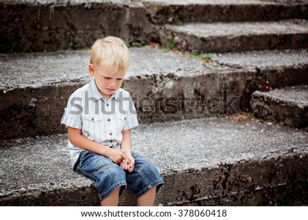 Little Boy crying  sitting on stone steps in park. Loneliness, melancholy, stress - stock photo