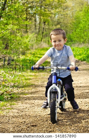 Little boy cycling his bicycle outdoor - stock photo